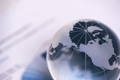 Globe with financial papers Stock Photos