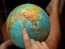 Traveling with a finger on the map globe. Globe and finger pointing to the place of future vacation, which is likely to be in Sri Lanka on Ceylon Island in stock photos