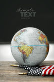 Globe and flag on school desk stock photography