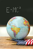 Globe and flag on school desk Stock Photos