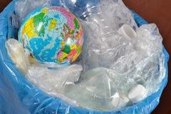 Globe in the garbage bin Stock Images