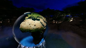 The globe with glass oceans over the lake between trees at night with full moon. And lights stock video
