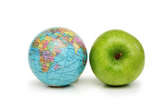 Globe and green apples Stock Images