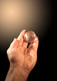 Globe At Hand. Glass globe lying at human hand on gradient background with copy space Stock Image