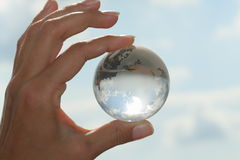 Globe in hand. On blue sky Royalty Free Stock Image