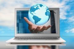 Globe in hand through laptop Stock Photos