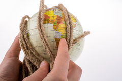 Globe in hand wrapped with rope Royalty Free Stock Photography