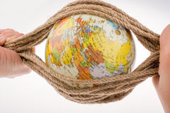 Globe in hand wrapped with rope Stock Image
