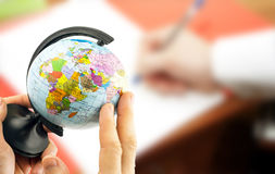 Globe in the hands on the background blurred office background Royalty Free Stock Images
