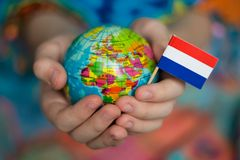 Globe in hands with the flag of the Netherlands royalty free stock photos