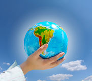 Globe in hands under blue sky Stock Photos