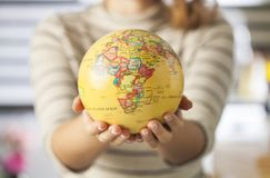 Globe in hands. Woman hand holding an earth toy globe stock photo