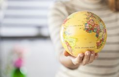 Globe in hands. Woman hand holding an earth toy globe royalty free stock images