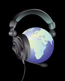 The globe in the headphones. With a microphone on a black background Stock Photo
