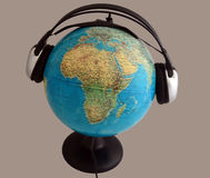 Globe with headphones. Globe with headphones listens to music Stock Image