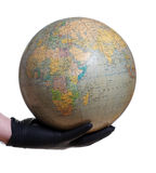 Globe holding in hand with glove. On white royalty free stock images