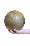 Globe holding in hand with white glove. On white royalty free stock images