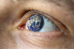 Globe hope. Close-Up of a male face with the earth in the eye (asia view). Symbolise Hope, fear of climate change, natural disasters like flood...etc. Earth view stock image