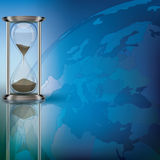 Globe and hourglass on blue Stock Photography