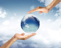 Globe in human hand against blue sky. Royalty Free Stock Photography