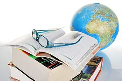 Globe. Image of a globe and a pile of books representing world news with glasses royalty free stock photography
