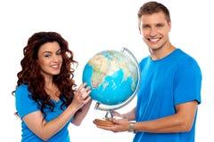 Globe joyeux de fixation de couples et sourire à l'appareil-photo Image stock