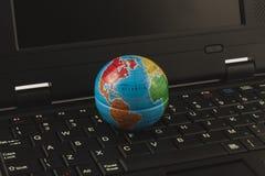 Globe on the keyboard. Little globe on the black keyboard of notebook Stock Photos