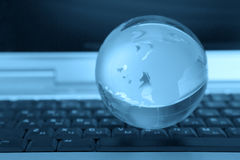 Globe and keyboard. The glass sphere of a planet lies on the computer keyboard in dark blue color Royalty Free Stock Photography