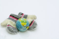 Globe and knitted mittens in snow Royalty Free Stock Image