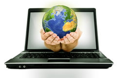 Globe from laptop. Hands with Earth coming from laptop screen Stock Photos