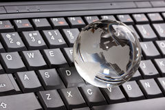 Globe on laptop keyboard Stock Image