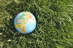 Globe lies on green grass Royalty Free Stock Photos