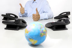 Globe and like hand with office phones on desk, global internati Royalty Free Stock Photography