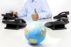 Globe and like hand with office phones on desk, global international support Royalty Free Stock Photo