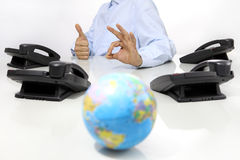 Globe and like hand with office phones on desk, global international support Royalty Free Stock Images
