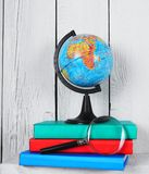 The globe, magnifier and books . Royalty Free Stock Images