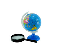 The globe and magnifying glass Stock Image