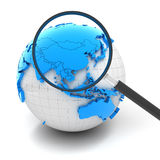 Globe with magnifying glass over China and Asia Stock Images