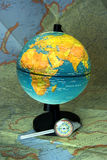 Globe on map. Globe on large map, with distance meter Royalty Free Stock Image