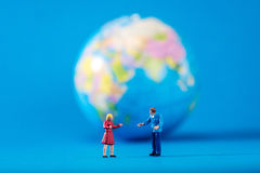Globe and miniature people Royalty Free Stock Photos