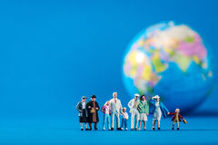 Globe and miniature people Stock Photos