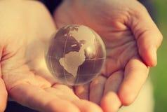 Globe modèle de verre cristal de participation dans des mains avec soin Photos libres de droits