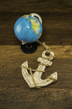Globe model with old white anchor on wooden background. Globe model with old white anchor with rope around  on wooden background Stock Photos