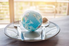 Globe model placed on plate with fork, menu in famous hotels. In stock photos