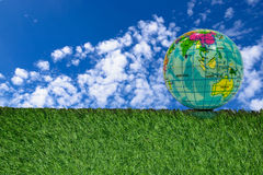 Globe model rests on the green grass. Stock Image