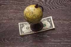 Globe and money. Globe and money on a background of a wooden cover royalty free stock photo