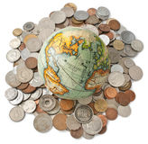 Globe Money Coins Isolated. A world globe resting on a pile of mixed coins from all around the world Stock Photo