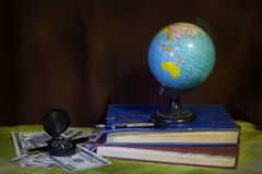 Globe with money,compass and book Royalty Free Stock Image