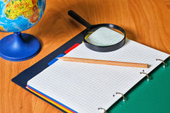 Globe, notebook, pencil and magnifying glass on desk. Stock Photos