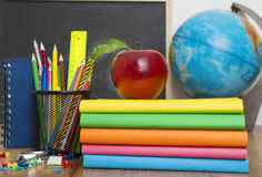 Globe, notebook stack and pencils. Schoolchild and student studies accessories. Royalty Free Stock Photo
